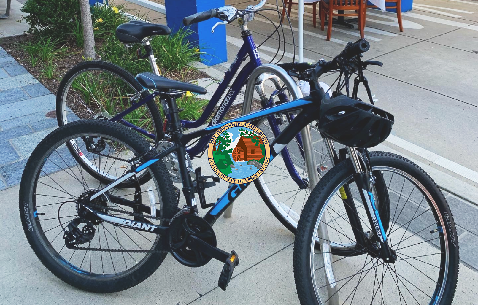 Two blue bicycles locked to a pole in Downtown Millburn near white outdoor dining tent
