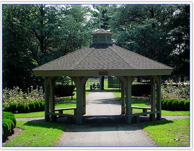 A black wooden gazebo in a park