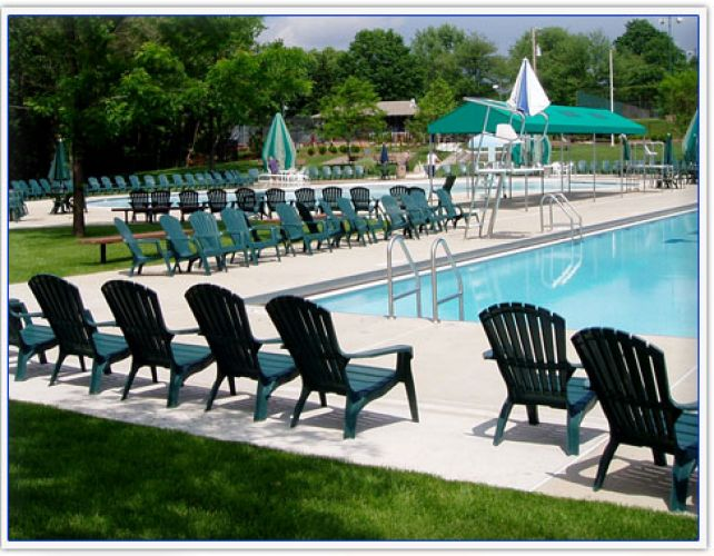 Rows of chairs surrounding a still swimming pool